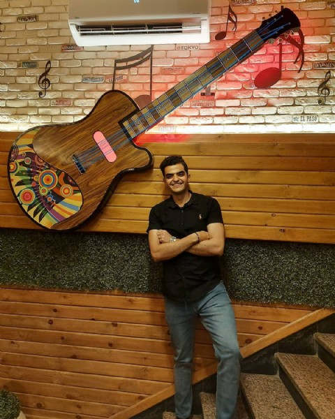 Photo by Abdo Siam in Red Wings. May be an image of 1 person, standing, guitar, brick wall and indoor.